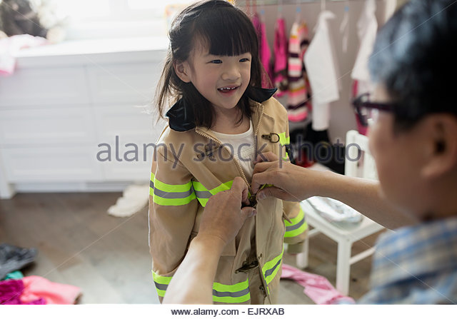 Grandfather putting firefighter costume on granddaughter in bedroom - Stock Image