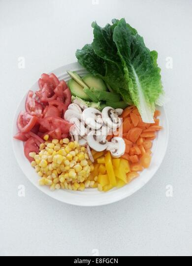 Raw fruit and vegetables on plate - Stock Image
