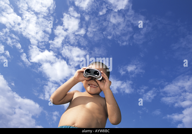 Boy looking at binoculars with blue sky in the background - Stock-Bilder