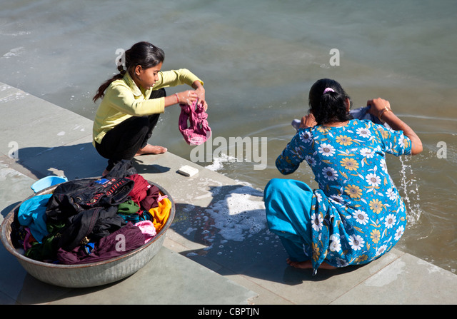 Mother and daughter doing the laundry.Pichola lake.Udaipur.India - Stock-Bilder