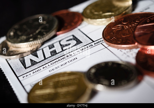 NHS Budget Cuts concept - A generic NHS payslip pay slip with British coins of the realm shot on a black background - Stock Image