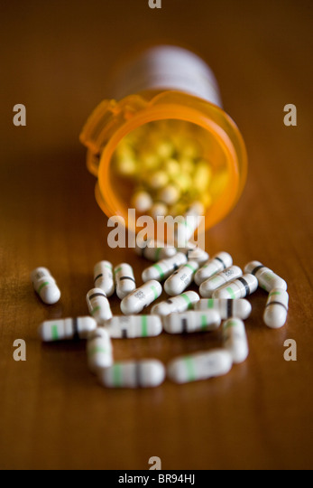 drug capsules pouring out of prescription bottle, white and black, drug, prozac medicine medication - Stock Image