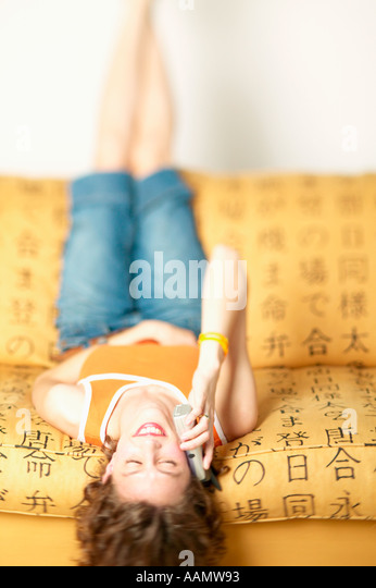 Woman talking on cell phone while laying upside down - Stock Image
