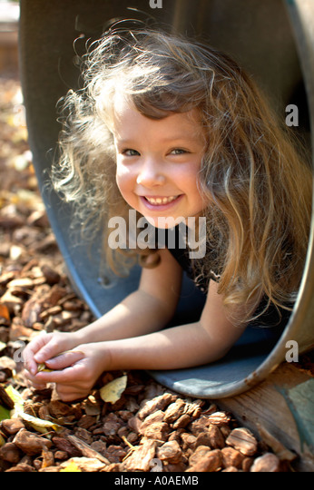 A cute little girl in a playground barrel. - Stock Image