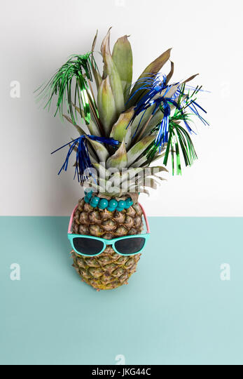Playful pineapple wearing sunglasses and palm cocktail on a pop bi-color background turquoise and white like horizon. - Stock Image
