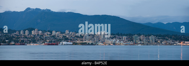 skyline of north Vancouver at dusk, British Columbia, Canada, from Stanley Park - Stock Image