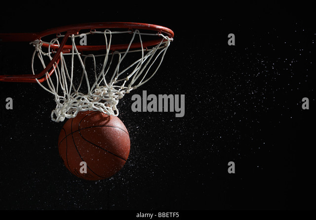 Basketball going through hoop - Stock Image