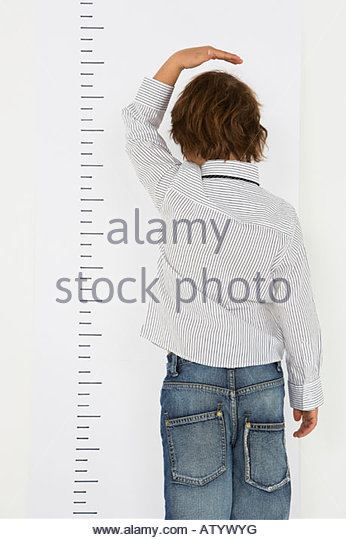 Young boy indoors measuring his height on a wall - Stock-Bilder