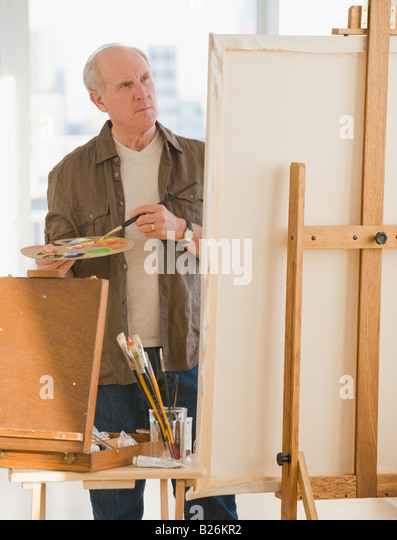Senior man painting on easel - Stock Image