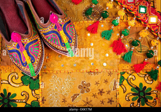 Colorful ethnic shoes and gipsy belt on yellow Rajasthan cushion cover on flea market in India - Stock-Bilder