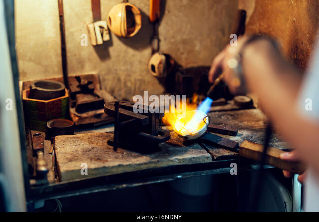 Jeweler welding gold the traditional way - Stock Image