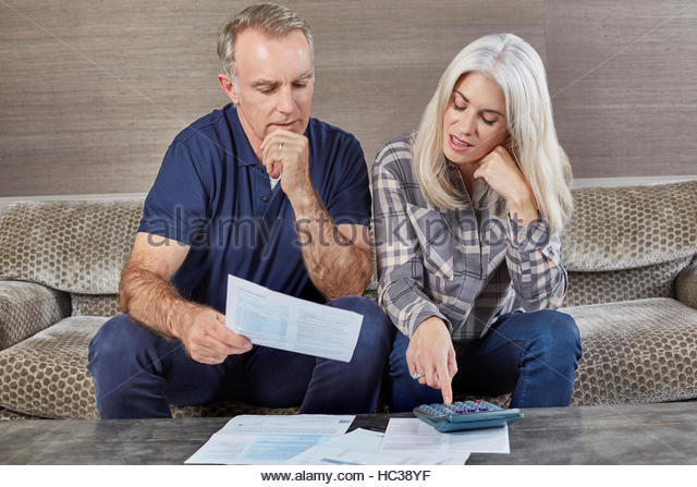 Mature married couple working from home together. - Stock Image