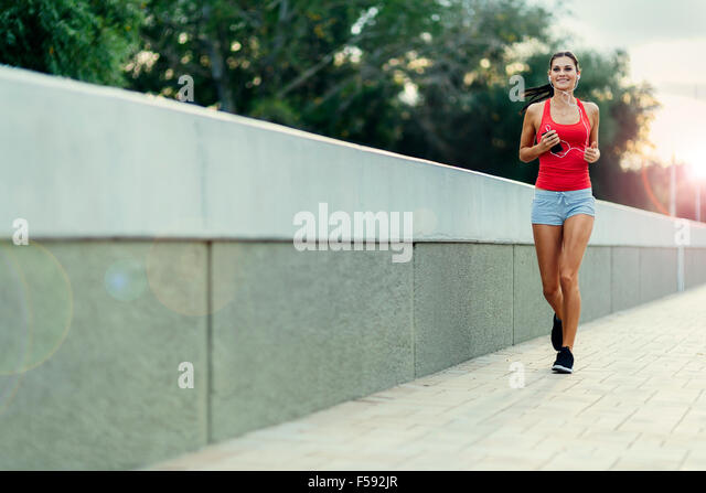 Healthy woman jogging in city entertained by music comming through her earphones - Stock Image