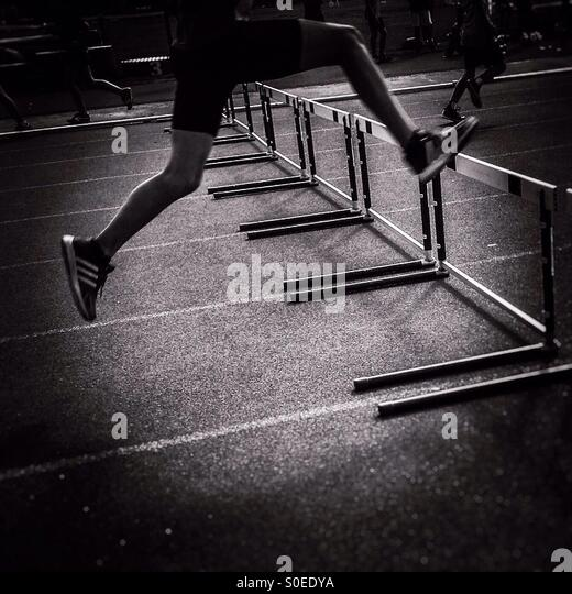 Athlete jumping hurdles - Stock Image