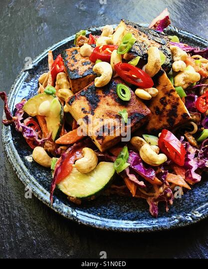Spicy pan-fried tofu with sobs noodle salad and peanut sauce - Stock Image