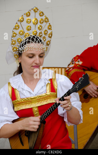 Ukraine, Yalta, Livadia Palace. Ukrainian folkloric show. Woman in traditional costume playing Russian three-stringed - Stock Image