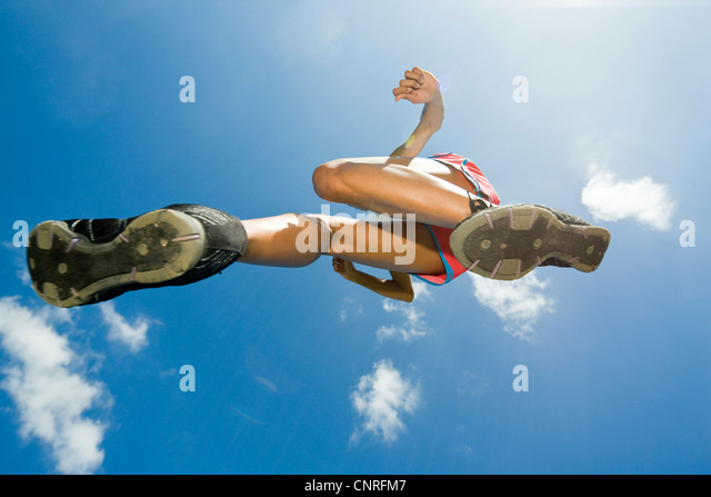 Female athlete jumping in air, directly below - Stock Image