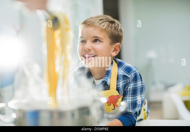 Boy smiling in kitchen - Stock Image