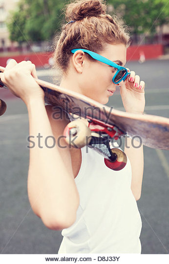 Young biautiful woman in blue sunglasses standing on the playground with a skateboard in her hands in the daytime. - Stock Image