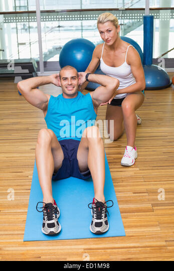 Trainer assisting man with abdominal crunches at fitness studio - Stock Image