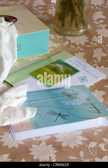 Sympathy cards and box of tissues on tablecloth - Stock Image