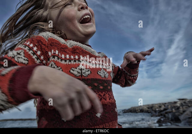 Little girl running on a rocky beach - Stock Image