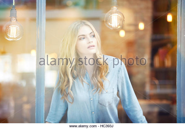 Young woman looking out window. - Stock-Bilder