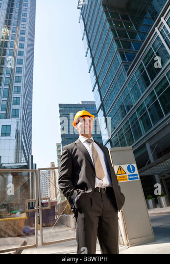Shot showing a man dressed in a suit and hard hat on a costruction site in a modern city environment - Stock Image
