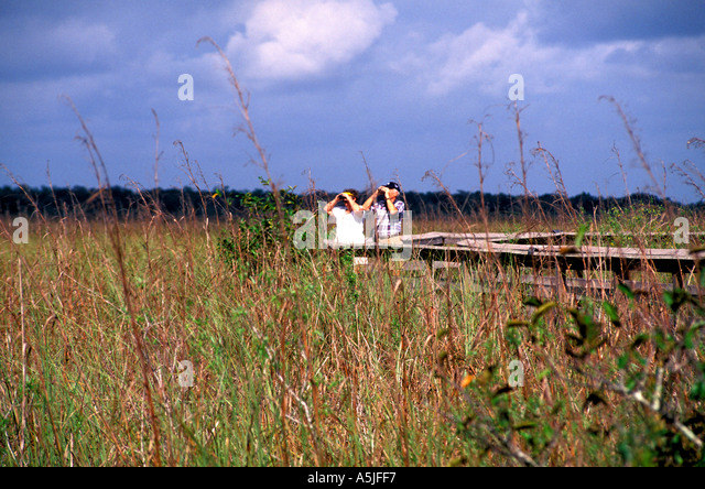 Florida Everglades National Park elderly couple viewing wildlife Anhinga Trail boardwalk - Stock Image