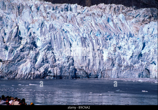Alaska cruise ship Glacier Bay cruise ship passengers view large huge blue ice glacier cold - Stock Image
