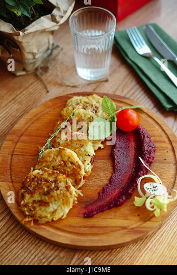 Hash browns and sauce on wooden tray - Stock Image