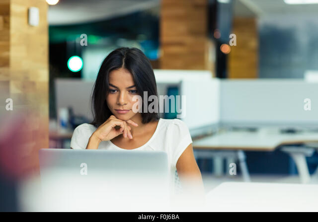 Portrait of a serious businesswoman using laptop in office - Stock Image