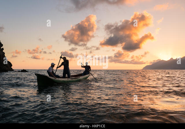 Fishermen paddling a dugout canoe off Brazil - Stock Image