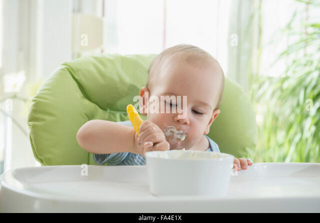 Cute little baby boy eating food on high chair, Munich, Bavaria, Germany - Stock Image