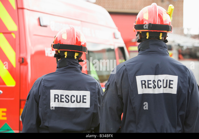 Two rescue workers standing near rescue vehicle - Stock Image