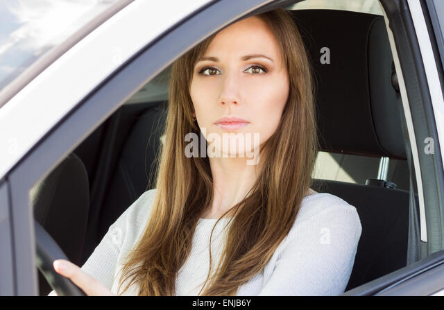 Young serious woman in car. Beauty caucasian adult girl drive a car - Stock Image