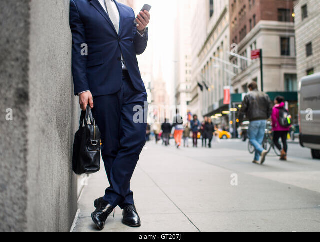 Low section of businessman holding bag and using smart phone while standing on sidewalk - Stock-Bilder