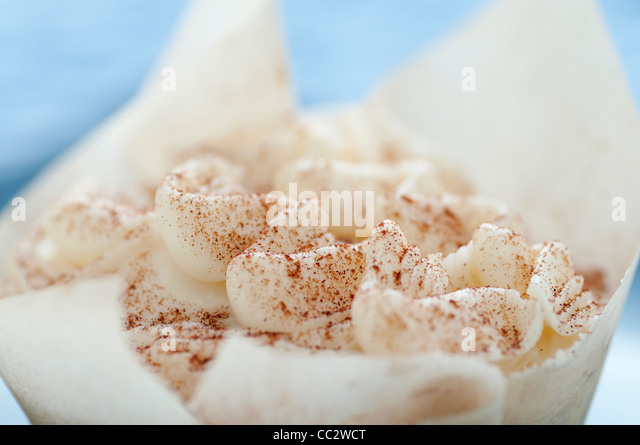 Bakery cupcake with buttercream frosting and cinnamon in parchment - Stock Image