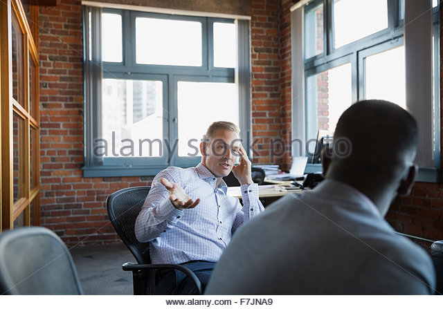 Businessmen talking in office - Stock Image