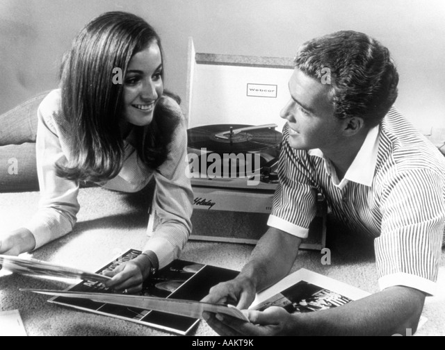 1960s TEEN COUPLE PLAYING LP VINYL RECORDS ON PORTABLE PHONOGRAPH - Stock Image