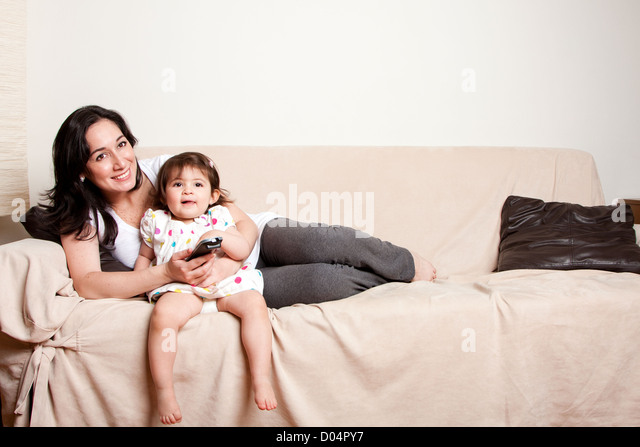 Beautiful happy family mother and baby toddler daughter sitting relaxed laid back on sofa couch in livingroom watching - Stock Image