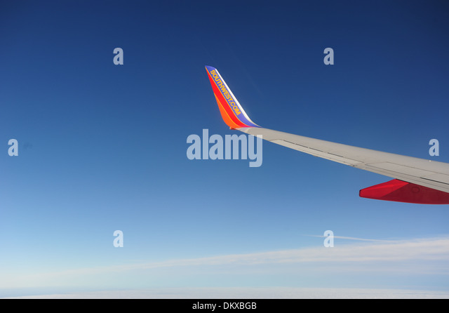 Southwest Airlines wing with winglet on the wing of Boeing 737-700 jet aircraft in flight over clouds - Stock Image