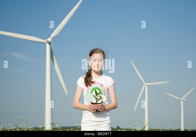 Girl with plant by wind turbines - Stock Image