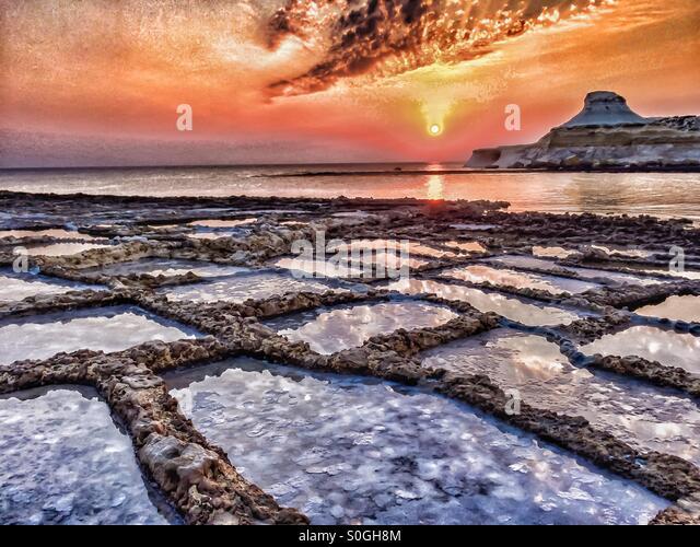 Dramatic sunrise over salt pans and calm sea - Stock Image