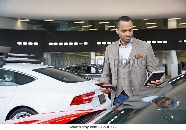 Man looking at color swatches in car dealership - Stock Image