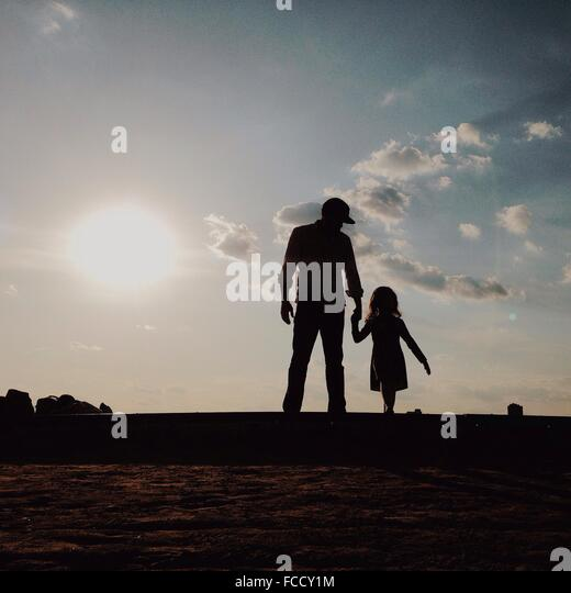 Silhouette Father With Daughter Standing On Field Against Sky - Stock-Bilder