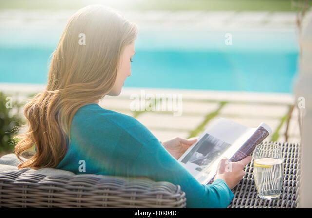 Brunette woman reading magazine at luxury poolside - Stock Image