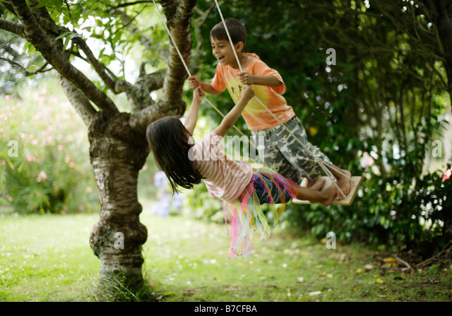 Brother and sister on swing together aged six and five years - Stock Image
