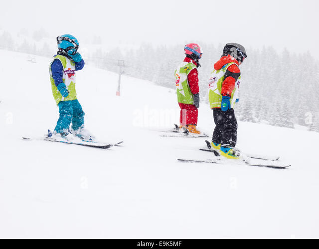 group of young children  wearing helmets and goggles learning to ski in a group lesson with  falling snow - Stock Image