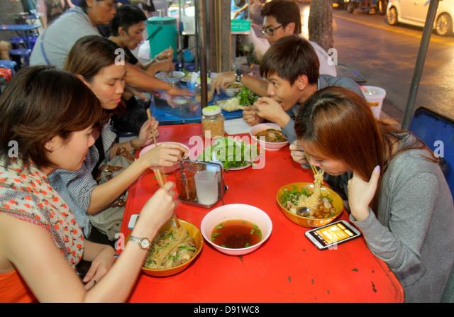 Thailand Bangkok Pathum Wan Rama 1 Road Asian man woman vendor food sidewalk tables eating dining - Stock Image